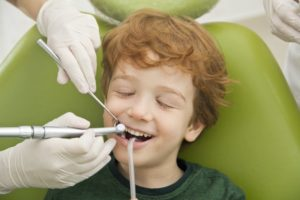 boy smiling getting dental cleaning