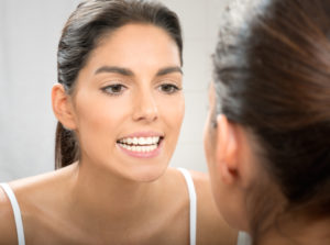 Woman examining healthy teeth in mirror